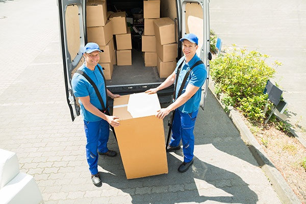 Movers loading packed boxes in truck
